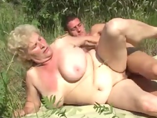 german granny outdoor with young man by troc